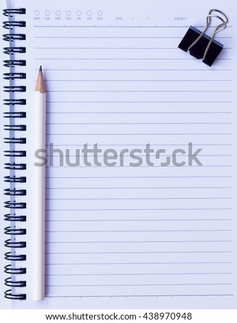 notebook paper with white pencil and black paper clip on white background for texture