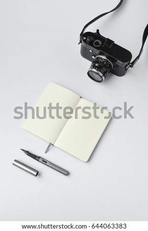 Notebook, pen, and camera, on white background - taken in natural light with strong shadow to create realistic indoor mood