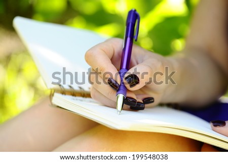 Notebook, pen and female hand close up. - stock photo