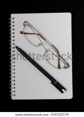 notebook, pen and glasses on a dark background