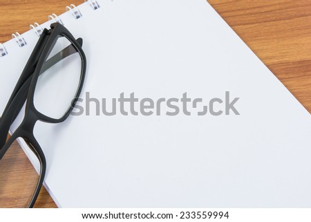 Notebook, pen and glasses on wooden table - stock photo