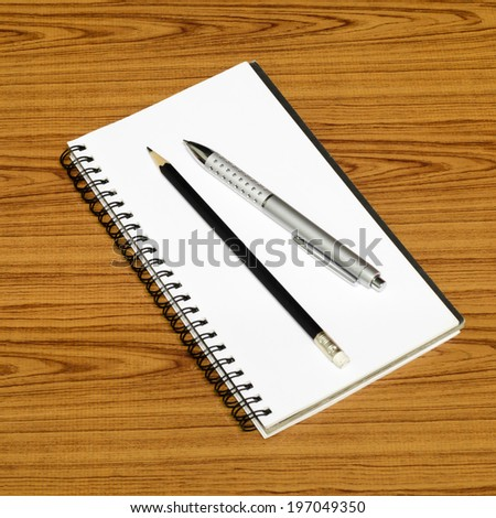 notebook pen and pencil on wood background
