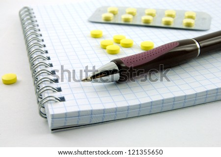 Notebook, pen and pills - stock photo
