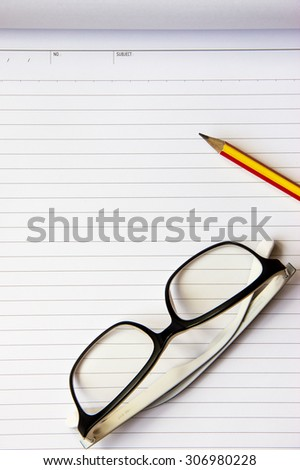 Notebook, pencil and eye glasses on wood background