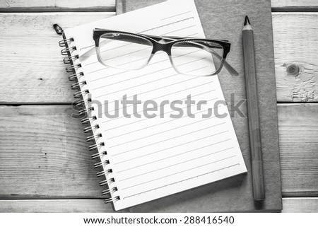 notebook , pencil and eyeglasses  on wood table ( black and white style ) - stock photo