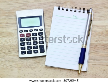 Notebook, silver bal lpen and calculator on wooden desk