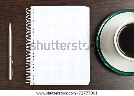 Notebook, silver pen and coffee in green cup on desk - stock photo