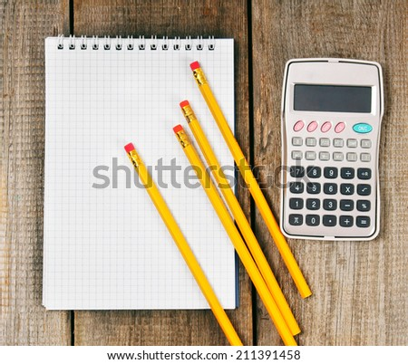 Notebook, the calculator and pencils on a wooden background.