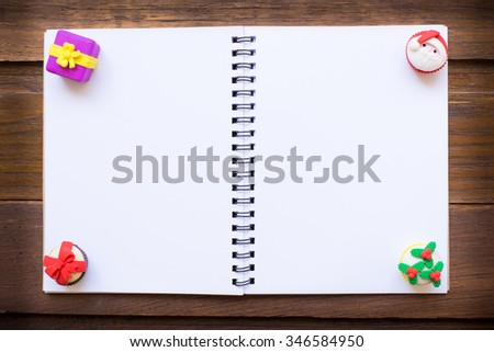 Notebook to display your artworks. with cute vintage christmas new year gifts mock up on wooden background