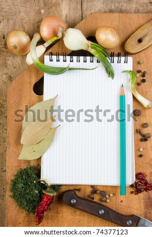 notebook to write recipes on the background of a cutting board with spices - stock photo