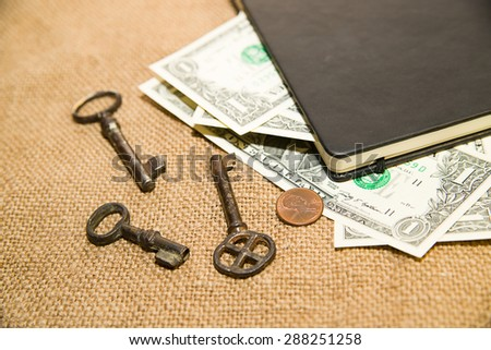 notebook with a blank sheet, key and money on the old tissue - stock photo