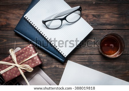 notebook with a glasses, present, laptop, magazine on wood desk. - stock photo