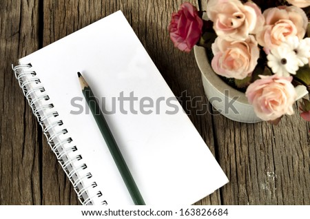 Notebook with artificial flowers in ceramic pots - stock photo