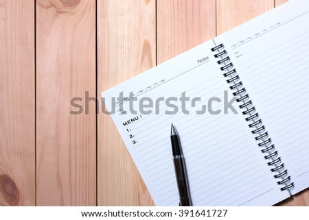 Notebook with black pen. Writing Menu with wooden pallet background.
