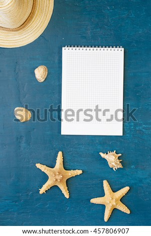 Notebook with blank pages with beach straw hat, sea shells and starfish on a blue surface, top view