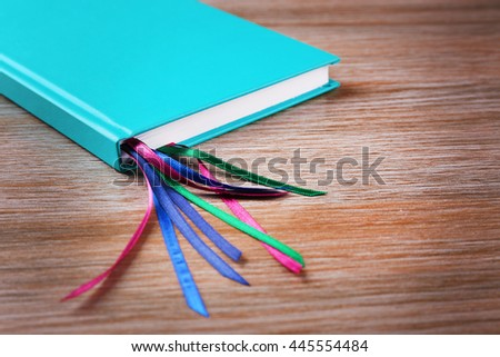 Notebook with bookmarks on wooden background - stock photo