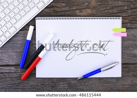 Notebook with Budget Cuts Handwritten on wooden background and Modern Computer Keyboard. Top View Composition