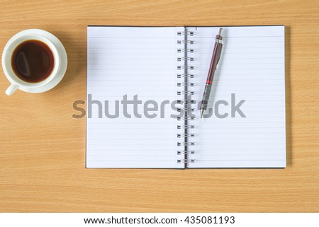 Notebook with coffee and pencil on wooden background