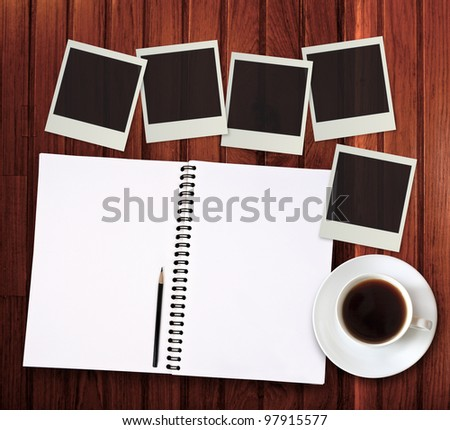 notebook with coffee and photo frame on wooden background