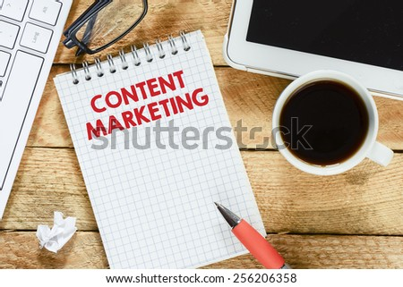 Notebook with content marketing. Workplace with keyboard , tablet pc , coffee, notebook with content marketing and pen on wood table - stock photo
