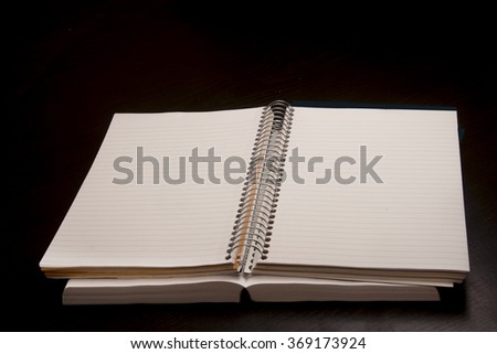Notebook with empty pages/Notebook/Plain notebooks on a black surface - stock photo