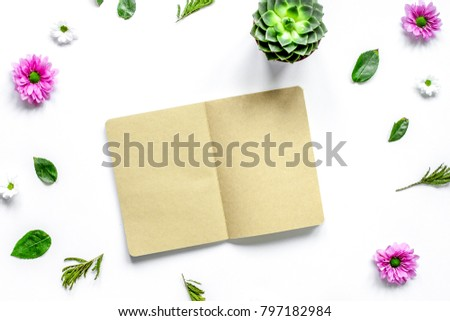 Notebook with flower petals on white table background top view m