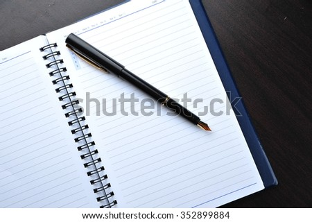 Notebook with fountain pen on wooden table - stock photo