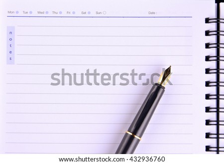 Notebook with fountain pen on wooden table