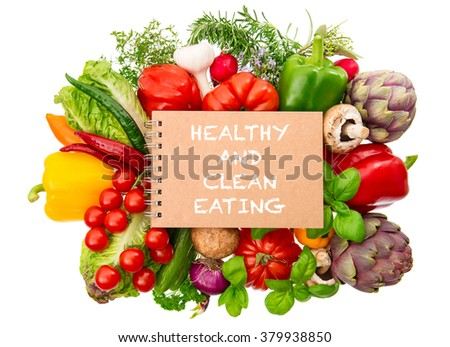 Notebook with fresh organic vegetables and herbs closeup isolated on white background. Healthy and clean eating concept - stock photo