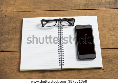 Notebook with glasses and smart phone on wooden background.