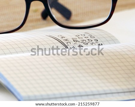 Notebook with graph paper, handwritten numbers and glasses