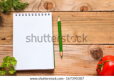 Notebook with green pencil, fresh herbs and tomato on wooden table