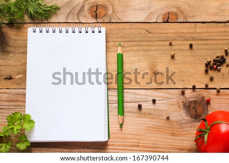 Notebook with green pencil, fresh herbs, spices and tomato on old wooden kitchen table
