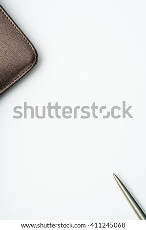 Notebook with leather cover and silver ballpoint pen  on white background.Copy space in the center from top view - stock photo