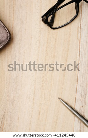 Notebook with leather cover, silver ballpoint pen and glasses on light brown wooden background. Copy space in the center from top view - stock photo