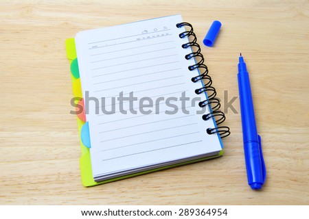 Notebook with pan on wooden background