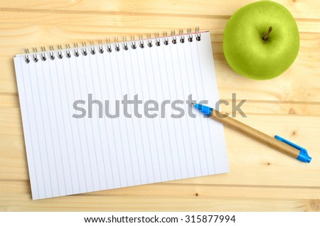 Notebook with pen and apple fruit on wooden table - stock photo