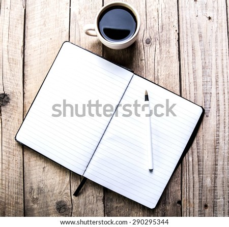 notebook with pen and coffee  on old  wooden table - stock photo