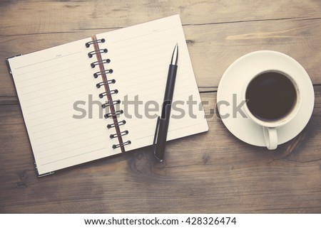 notebook with pen and cup of coffee on wooden table