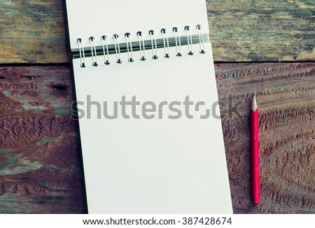 Notebook with pen and pencil on wooden table,Vintage - stock photo