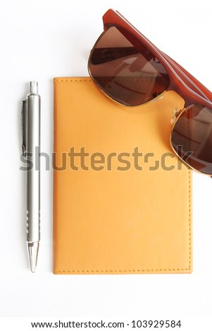 notebook with pen and sunglasses on white - stock photo