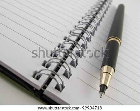 Notebook with pen - closeup - stock photo
