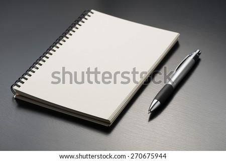 notebook with pen on black table - stock photo