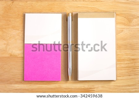 Notebook with pen on wood background - stock photo