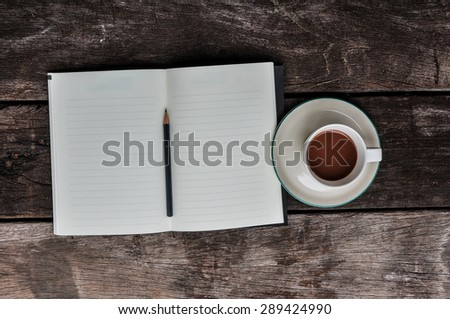 notebook with pencil and coffee cup on wooden background, business concept