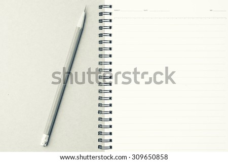 Notebook with pencil on wood background- vintage filter