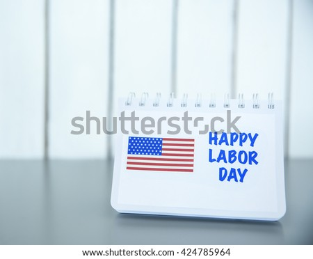 Notebook with printed text HAPPY LABOR DAY and American flag on wooden background