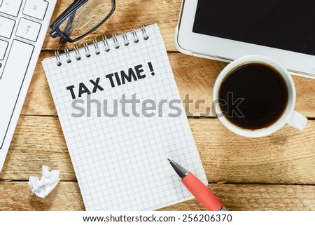 Notebook with tax time. Workplace with keyboard , tablet pc , coffee, notebook with tax time and pen on wood table - stock photo