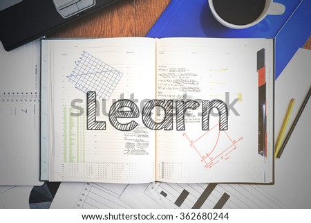 Notebook with text inside associated with the education - Learn . On table are coffee, laptop and some sheet of papers with charts and diagrams - stock photo