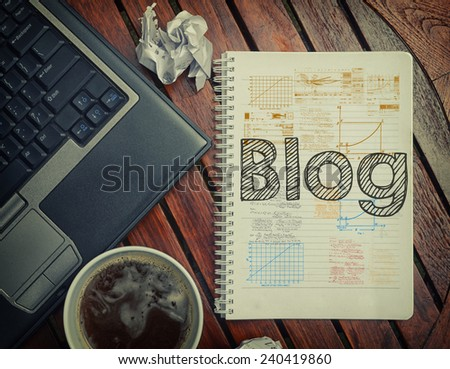 Notebook with text inside Blog on table with coffee, laptop pc and crumpled sheets - stock photo